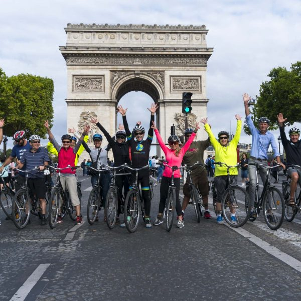 Tour group standing in front of Arc de Triumph with arms raised
