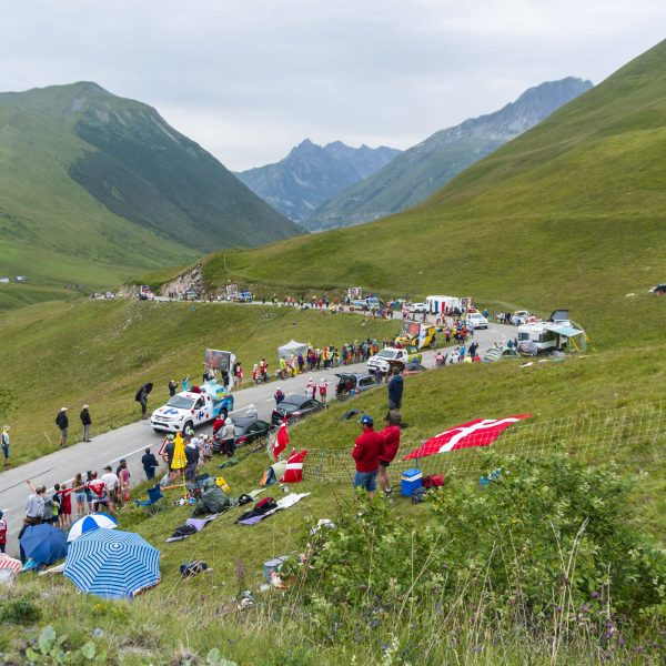 Spectators and cars line the side of the road
