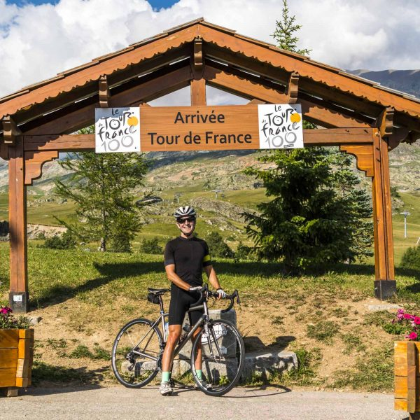 "Guest standing below the ""Welcome Tour de France"" sign"