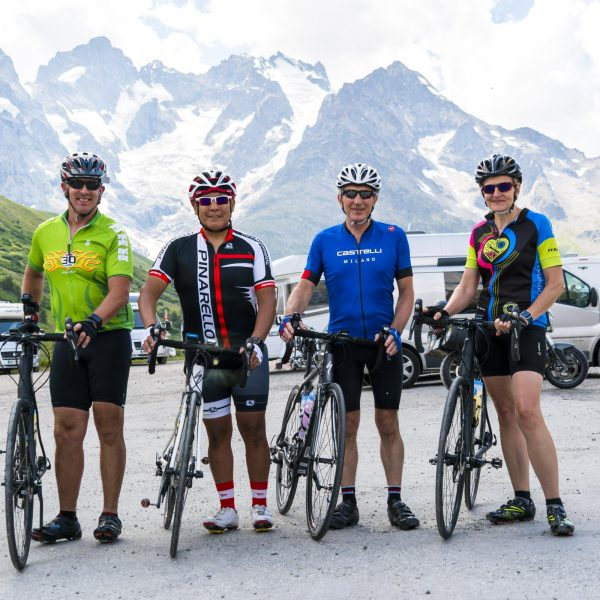 Cycling guests posing for a picture in front of snowcapped mountain range