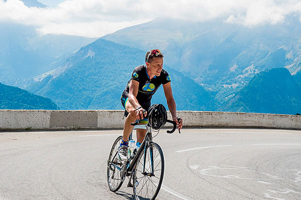 Simon Kessler Cycling with mountains in background